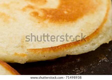 close up of drop scones or pancakes being fried in hot butter.