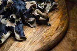 Close up of dry black sliced mushroom on wooden background. Edible dark fungus - auricularia polytricha. Nobody