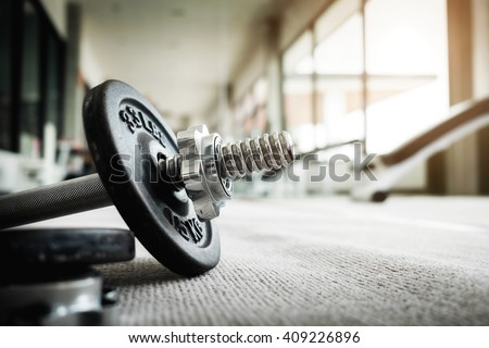 Close up of dumbbell exercise weights on the floor at fitness gym vintage tone.