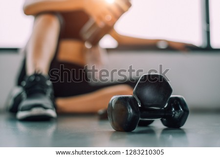 Close up of dumbbell with exercise woman lifestyle workout in gym fitness breaking relax after sport training with protein shake bottle background. Healthy lifestyle bodybuilding athlete muscles