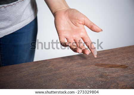Close-up of dust on woman finger taken from wooden table #273329804