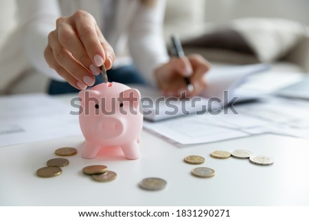 Close up of economical young woman manage household family budget calculate finances at home. Provident female put coin in piggy bank saving invest money for future payment. Investment concept.