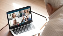 Close up of elderly man talk speak with diverse relatives on video call using modern tablet quarantine at home, mature grandfather have online web conversation conference with family on computer