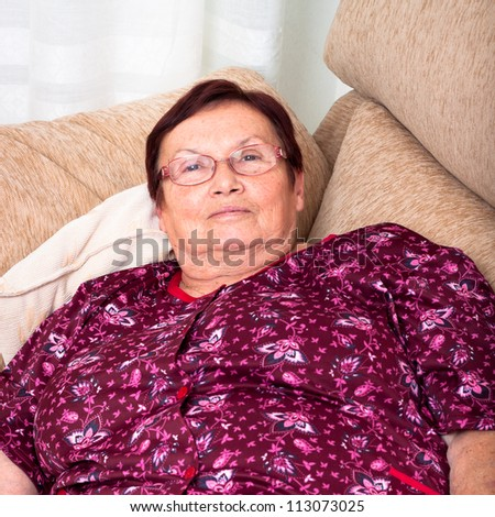 Close up of elderly woman relaxing on sofa.