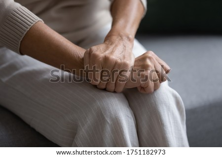Close up of elderly woman sit on sofa with hands clenched joined on laps making difficult decision, pensive mature female thinking pondering, feel lonely or anxious at home or retirement house alone Stock foto ©