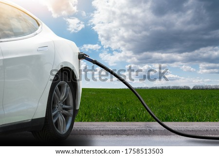 Close up of electric car with a connected charging cable on a background of green field