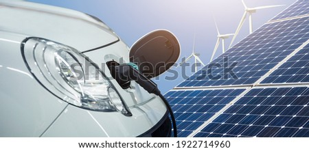 Close up of electric car with a connected charging cable on the background of solar panels and wind turbines - sources of clean renewable energy Foto stock ©