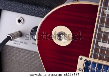 Close up of electric guitar toggle switch with vintage amplifier and patch cable