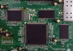 Close-up of electronic circuit board PCB with components: microchip, processor, integrated circuits, capacitors, resistances and electronic connections are noted. High-quality macro