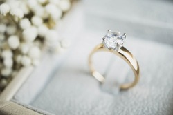 Close up of elegant diamond ring in the box with white flower background. soft and selective focus.love and wedding concept.