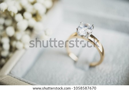 Photo of  Close up of elegant diamond ring in the box with white flower background. soft and selective focus.love and wedding concept.