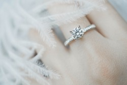 Close up of elegant diamond ring on the finger with feather and gray Scarf background. Diamond ring.