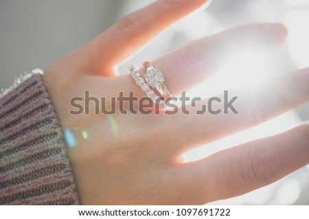 Close up of elegant diamond ring on woman finger with dark pink sweater winter clothe and sunlight tone. love and wedding concept.soft and selective focus.