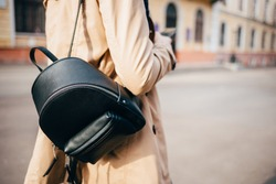 Close-up of elegant women's backpack. Rear view of young woman dressed in beige coat and with black bag walking down street in city.