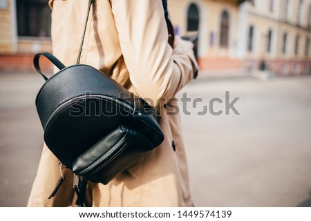 Close-up of elegant women's backpack. Rear view of young woman dressed in beige coat and with black bag walking down street in city. Foto stock ©