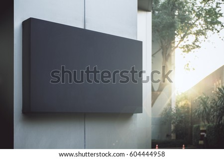 Close up of empty black poster on concrete building. Trees and sunlight in the background. Mock up