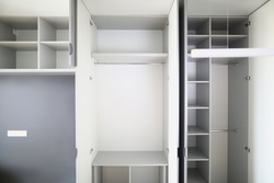 Close-up of empty closet space in room. Many shelves and expanse. Cupboard or wardrobe for people clothes. New purchased property. Moving day and renovation concept