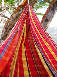 Close up of Empty Hammock Textile in Perspective. Brightly colored striped cotton fabric in West Indies hanging lounger. Colorful sturdy fabric pattern.