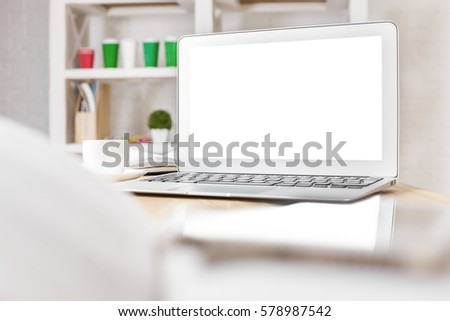 Close up of empty white laptop, coffee cup and supplies on office desktop. Mock up