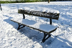close up of empty wooden park bench covered in snow following a deep snow fall. outside on a sunny cold winter's day