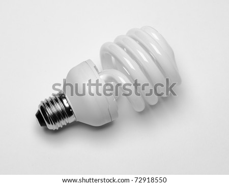 close-up of energy saving compact fluorescent light bulb with shadow on white background