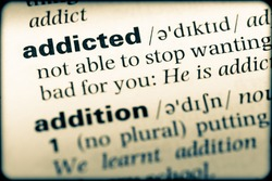 Close up of English dictionary page with word addicted