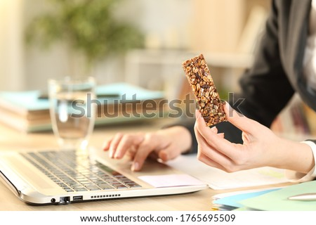Close up of entrepreneur woman hands holding cereal snack bar working on laptop at home office