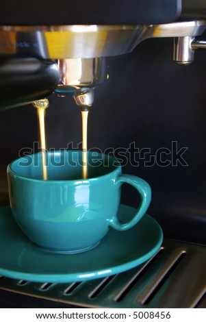 Close up of  espresso machine dispensing coffee into a green cup.