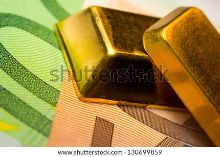 Close-up of euro banknotes and two gold ingots
