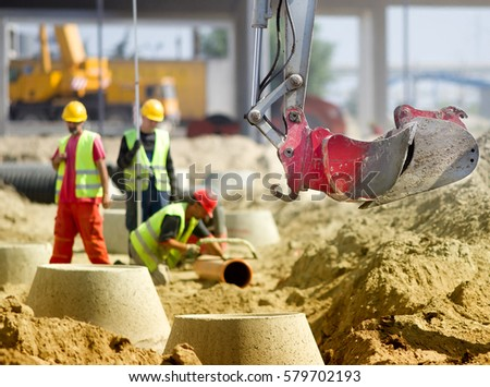 Close up of excavator bucket and workers working on manhole and sewerage pipes in background at construction site