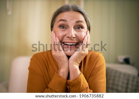 Close up of excited amazed middle aged woman with blue eyes and wrinkles holding hands on her face looking at camera in astonishment, being overjoyed with pleasant news. Positive human  ストックフォト ©