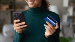 Close up of excited young Caucasian woman hold smartphone shop online with credit card. Happy female client or buyer pay buy on internet with cellphone using secure banking system on gadget.