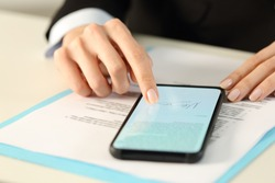 Close up of executive woman hands signs contract on smart phone with finger sitting on a desk