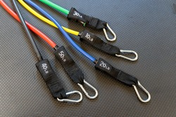 Close up of exercise resistance bands of various colors and weighted pound resistance.
