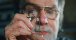 Close up of experienced goldsmith controlling a quality of diamond stone, selected for making jewels in workshop. Concept of jewelry,luxury,goldsmith, diamonds, brilliance.
