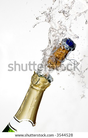 Close-up of explosion of champagne bottle cork with white background