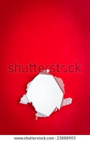 Close up of exposed white hole torn in red background.