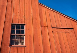 Close up of exterior red wooden barn with a 12-pane antique window background against a blue sky.