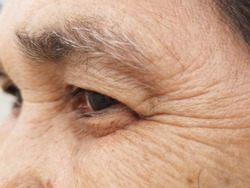 Close up of eye and grey eyebrown of an old woman showing crow's feet and wrinkles from aging