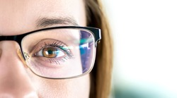 Close up of eye and woman wearing glasses. Optometry, myopia or laser surgery concept. Brown eyed girl with spectacles and eyeglasses. Macro portrait of face and specs. Light reflection on lens.