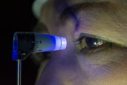Close up of eye examination, ocular pressure measurement with applanation tonometer in dark room.