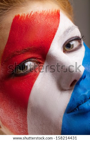 Close up of face art. Netherlands flag is painted on woman face
