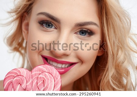 Close up of face of cheerful woman touching candy to her lips. She is smiling and looking at the camera with desire