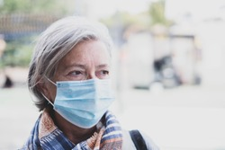 close up of face of mature woman looking away wearing medical mask prevention coronavirus or covid-19 or another type of virus - senior portrait and close up with medicine mask on the face