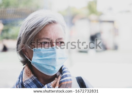 close up of face of mature woman looking away wearing medical mask prevention coronavirus or covid-19 or another type of virus - senior seriously worried and prevention be infected - pandemic problem