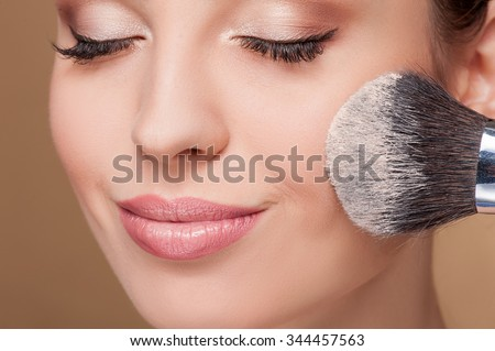 Close up of face of young woman getting powder on her cheek with a brush. She is smiling. Her eyes are closed