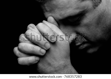 Close up of faithful mature man praying, hands folded in worship to god with head down and eyes closed in religious fervor. Black background. Concept for religion, faith, prayer and spirituality. - Shutterstock ID 768357283