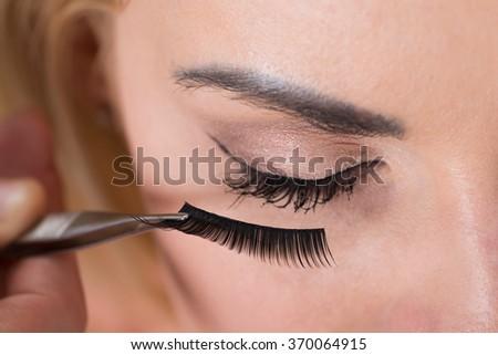 Close-up of false eyelashes being put on woman's eye