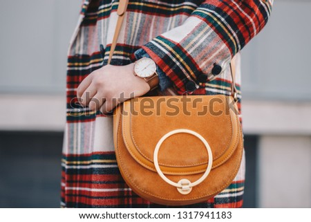 Close-up of fashion details, stylish young fashion blogger wearing an overcoat with a chequered pattern and a wrist watch while holding a fancy camel bag.