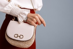 Close up of fashionable elegant woman`s outfit: trendy small shoulder bag, stylish wrist watch, beautiful ring with red gem. Copy, empty space for text